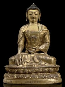 A gilt repoussé bronze figure of Buddha, Qianlong mark and period (1736-1795).